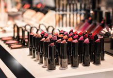 Different colors of lipstick and eye shadow on the shop window in the cosmetic store. Test sample. Front view stock images