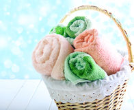 Different colors towels in wicker basket. Over light background royalty free stock photography