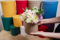 Different colors.. Work florist, bouquet in a round box. smelling flowers holding peach roses in hat against the Royalty Free Stock Photography
