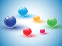 Different colour glass balls on blue background Stock Images