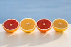 Different colour grapefruits. On sea view background Stock Photos