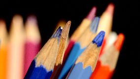 Different colour pencils isolated on black stock video footage