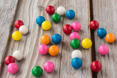 Different coloured bubble gum scattered on an old rustic wood background Royalty Free Stock Images