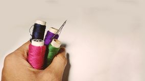 Different colours thread rolls with needle in hand of a tailor. royalty free stock image