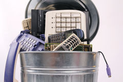 Different computer parts in trash can. Different computer parts and phone in trash can Royalty Free Stock Image