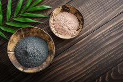 Different cosmetic clay. In coconut bowls on wooden background, top view Stock Images