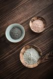 Different cosmetic clay. In coconut bowl on wooden background top view Stock Photo