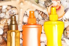 Holiday at sea cosmetic essentials. Different cosmetic sunscreen products on shells with starfish. Skin care cosmetics for safe tan. Beach sea holiday essentials royalty free stock photo