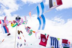 Different country flags weaving on a rope with a soccer ball in the center. Photo of a various country flags weaving on wind and royalty free stock images