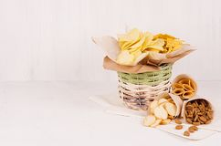 Different crispy golden snacks in wicker basket and paper cones on soft white wood background, with copy space. Different crispy golden snacks in wicker basket Royalty Free Stock Image