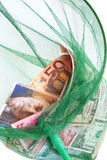 Different currencies caught in a fishing net Stock Photo
