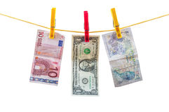 Different currency banknotes hanging on clothesline Royalty Free Stock Photos