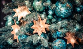 Different decorative Christmas-tree toys close-up, decorations for Christmas. Tree, green spruce branch needles, snow snowfall snowstorm snowflakes. Winter royalty free stock image