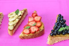different delicious toasts on green or pink crimson background. Healthy sandwich for breakfast or snack. Toast with raspberries, royalty free stock photo