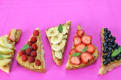 different delicious toasts on green or pink crimson background. Healthy sandwich for breakfast or snack. Toast with raspberries, stock photos