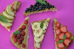 different delicious toasts on green or pink crimson background. Healthy sandwich for breakfast or snack. Toast with raspberries, stock image