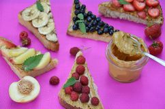different delicious toasts on green or pink crimson background. Healthy sandwich for breakfast or snack. Toast with raspberries, royalty free stock images