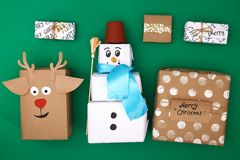 Different design of Christmas gifts from craft paper on a green background. Snowman, deer, stars, snow, handmade text. Handmade, stock photography
