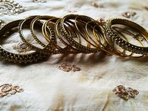 Different designed gold bangles in silk background stock photography