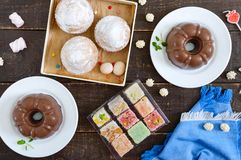 Different desserts on a wooden background. Chocolate pudding, muffins with icing sugar, Turkish delight. Top view, flat lay royalty free stock photography