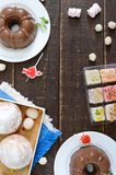 Different desserts on a wooden background. Chocolate pudding, muffins with icing sugar, Turkish delight. Top view, flat lay royalty free stock photo