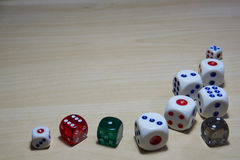 Different dices laying on the wooden table. Stock Photo