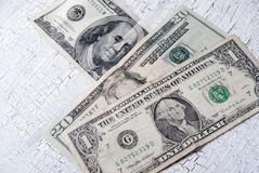 Different dollar bills on wooden table Stock Images