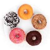Different donuts on white plate on white background top view royalty free stock photography
