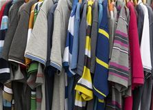Dresses at a shop. Different dresses and colors hanging on clothes hooks at a shop stock photo