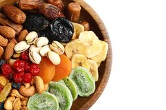 Different dried fruits and nuts in bowl on white background, closeup. Space for text royalty free stock photography