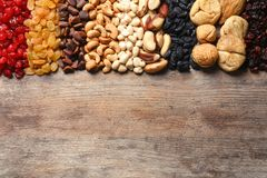 Different dried fruits and nuts on wooden background. Top view. Space for text stock images