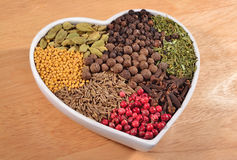 Different dry spices in plate in form of heart Stock Photography