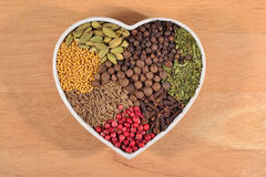 Different dry spices in plate in form of heart Royalty Free Stock Photos