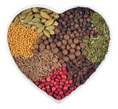 Different dry spices in plate in the form of heart on a white Stock Image