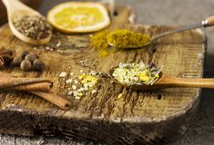 Different dry spices in spoons on old wooden board. The Different dry spices in spoons on the old wooden board Royalty Free Stock Images