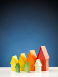 Different Eco Label Houses. Vertical image of two rows of miniature paper houses in energy label colors with a blue background royalty free stock photography