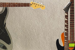 Different electric guitars on rough cardboard background, with plenty of copy space. Royalty Free Stock Photos