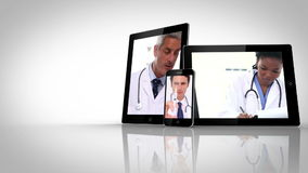 Different electrical devices showing doctors. On white background stock video footage