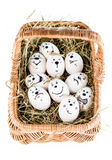 Different emotion faces. Made of white eggs in basket with hay Stock Photos