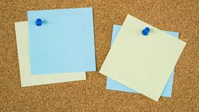 Different color post it notes pinned on cork board. Different empty colourful post it notes pinned on cork board stock photo