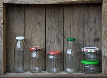 Different empty jar and bottles. On wooden background stock image