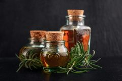 Different essential oils. In vintage bottles with cork on black background Stock Images
