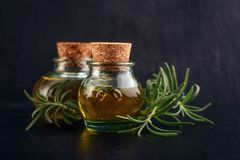 Different essential oils. In vintage bottles with cork on black background Stock Photos