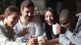 Diverse friends gathered in cafe watching funny video on smartphone