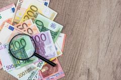 Different euros banknotes under magnifying glass. On desk Royalty Free Stock Images
