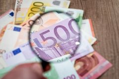 Different euros banknotes under magnifying glass. On desk Stock Photography