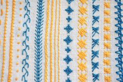 Different examples of yellow and blue patterns of embroidery on white fabric. Different examples of yellow and blue patterns of embroidery on a white fabric stock photo