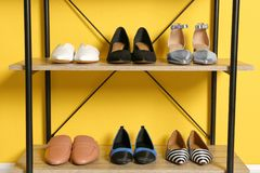 Different female shoes on shelf unit. Against color wall stock images