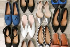 Different female shoes on wooden background. Top view royalty free stock photo