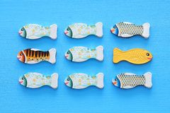 different fish swimming opposite way of identical ones. Courage and success concept.